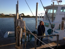 Me standing on a dock next to The Snappa, a charter fishing boat